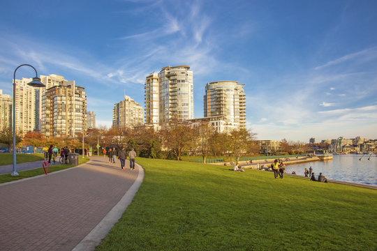 People on a sunny day in downtown Vancouver park by the ocean