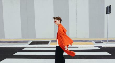 Alternative stylish young female on orange/red coat on street/minimalist composition.