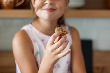 Close up of a smiling girl's hand holding a chocolate chip cookie