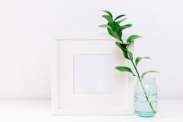 Mockup frame with a green branches in vase on table on minimal background. Home decor. Blog, website or social media concept.