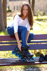 Portrait of a beautiful girl dresses roller skates while sitting