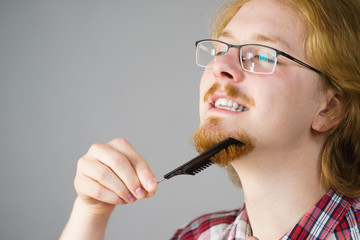Man brushing his beard using comb
