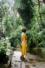 Back view of woman standing in tropic forest