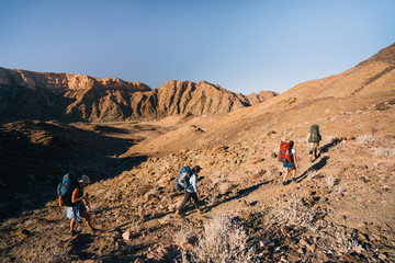 group of hikers hiking in a rugged desert canyon