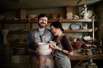 Happy potters family posing in small workshop