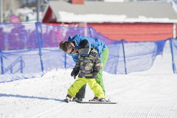 Ski Instructor Teaching a 3-Year Old Toddler Boy at a Mountain Resort