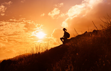Getting away from it all. Woman hiker sitting on mountain watching the sunrise.