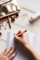 rose gold stationery tabletop, diary with hand writing an entry