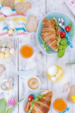 A family breakfast of croissants with rocket and cheese and aromatic coffee, eggs of different colors, bright dishes and Easter decor, ceramic rabbits. Fresh tulips of pink color.