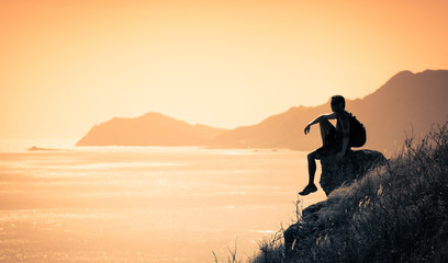 Young thoughtful man sitting on edge of mountain watching the sunrise.