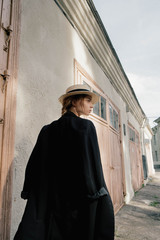 portrait of beautiful girl in hat and coat from the back