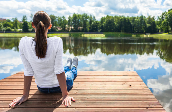 Young woman relaxing on a wooden dock by a beautiful lake. Outdoor getaways concept.