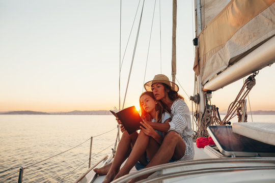 Mother and daughter reading a book together at sunset on a sailboat.