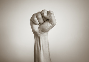 Closeup of fist clenched in the air. Power, victory, revolution concept.
