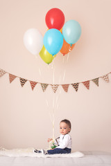 Cute little boy with his birthday balloons