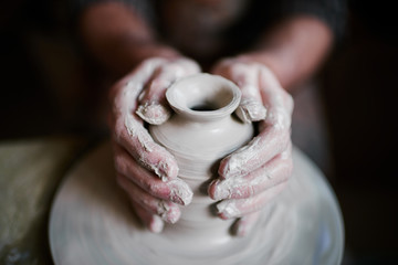 Potter shaping beautiful clay vase on wheel