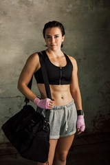 Strong brunette woman resting after boxing workout holding sport bag.