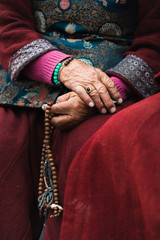 Tibetian  old lady in traditional costume holding mala beads in a hand. Ladakh,India