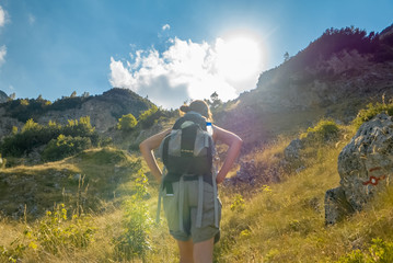 Young woman hiker on mountain adventure against sunset