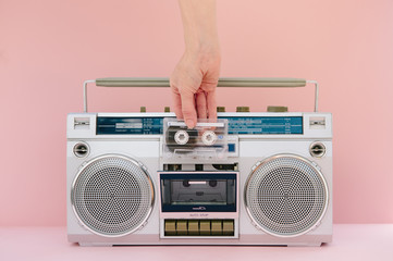 Hand inserting music tape into retro ghetto blaster tape deck over pastel pink background