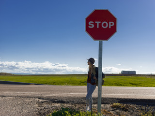Backpacker leaning on road sign
