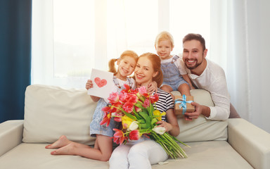 happy mother's day! father and children congratulate mother on holiday