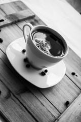Single white cup with black coffee on wooden table with few beans black and white photography