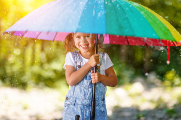 Happy child girl laughs and plays under summer rain with an umbrella.