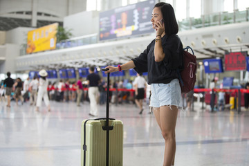 One young Asian woman in airport with suitcase