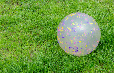 large colorful scratched plastic child's toy ball on a green lawn with copy space