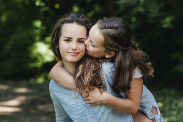 Sweet portrait of little girl giving her big sister a kiss