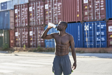 Handsome muscular athlete drinking water after exercise.