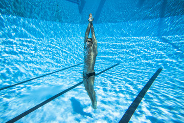 A fit young man swimming underwater