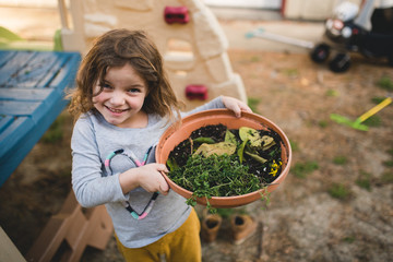 Portrait of small cute girl holding pot plant in spring