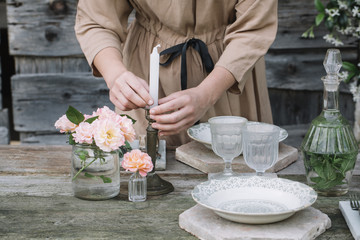 Woman setting table with candles