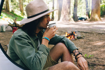 Portrait of a man drinking coffee at a camp site.