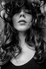 black and white portrait of beautiful sexy curly-haired girl with freckles