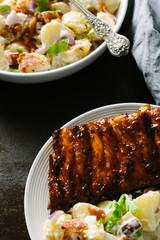 Plate of ribs with bowl of potato salad