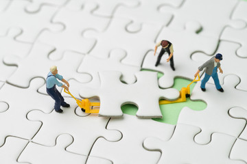 Teamwork, fulfill the missing piece for business success strategy concept, miniature workers team help using the forklift to complete the missing white jigsaw puzzle piece on pastel green background