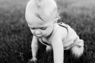 black and white image of a baby crawling in grass on a summer day