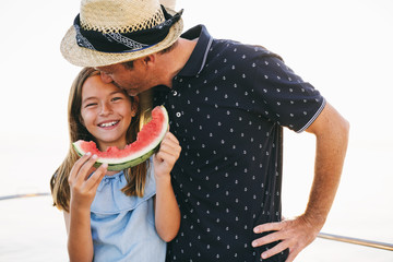 Father and daughter eating a watermelon slice on a sailboat.