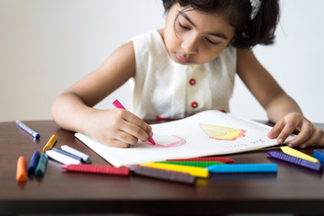Little girl drawing picture of ice cream and coloring