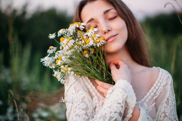 Front view portrait of beautiful young female with tender smile  and closed eyes holding the bouquet of camomile near her face