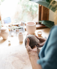 woman forming clay and creating beads and pinch pot by hand from raw materials in home studio workshop