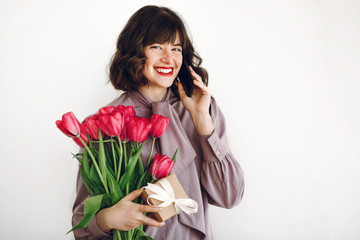 happy stylish girl talking on phone and holding pink tulips and gift box with ribbon on white background. happy mothers or womens day concept. young hipster woman smiling with flowers