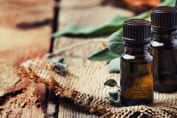 Essential sage oil in brown bottle on the vintage wooden blackground, rustic style, selective focus