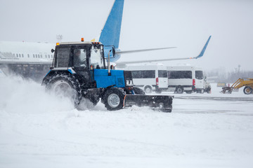 Clearing airport from snow during snow storm. clearing runway from snow. Clearing snow with bulldozers from airport aprons.