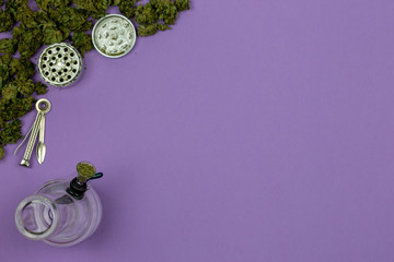 Loose medical marijuana with glass bong, metal grinder and cleaning tool on ultraviolet surface