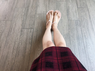 Woman Feet Wearing Pink Sandals and Scot Dress of Fashion. Selfie of Feet and Legs in Pink Shoes Isolated on Wooden Background Great For Any Use.