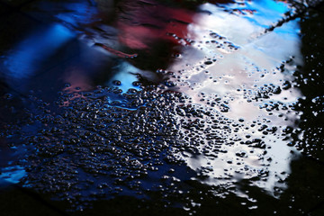 color reflection in the asphalt after the rain in the evening